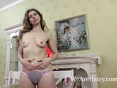 Elza strips naked in bedroom and models on a chair