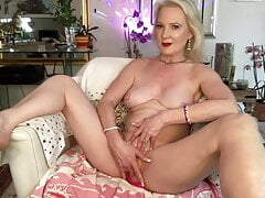 Mature blonde caresses her pussy on camera