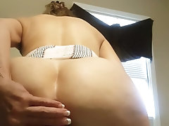 Plugs asshole while giving herself cock from behind