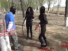 Two queens wearing leather boots whipping slaves